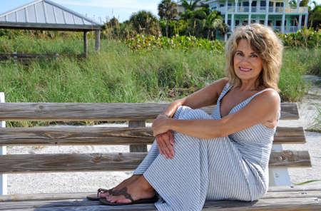 ベンチに座って魅力的な成熟した女性