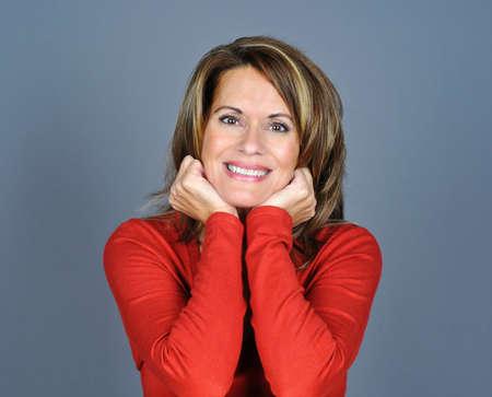 Portret van een volwassen vrouw met haar kin en glimlachen Stockfoto