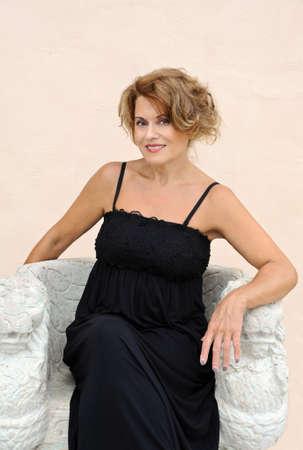 스톤 벤치에 앉아있는 아름다운 성숙한 여인 스톡 콘텐츠