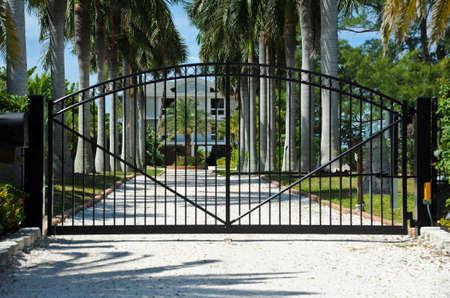 Iron Beveiligingsantennes beschermen de ingang van een Palm bomen omzoomde oprijlaan Stockfoto - 28042221