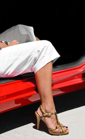 Womans leg in high heel shoes getting out of a car