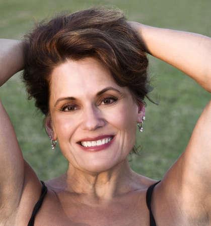 Aire libre Retrato de una mujer madura hermosa que saca el pelo hacia atrás, a la luz de la última tarde Foto de archivo - 46880290