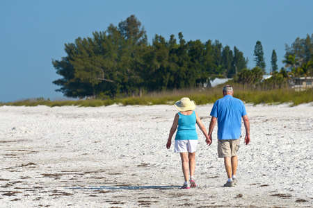 HOLMES BEACH, ANNA MARIA ISLAND, FL / USA - May 1, 2018: Senior Couple holding hands while taking an early morning walk on the beach. 에디토리얼