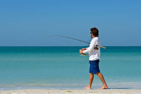 HOLMES BEACH, ANNA MARIA ISLAND, FL/ USA - May 1, 2018: A young man on the beach holding a fish he just caught while fishing in the Gulf of Mexico.