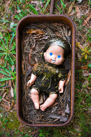 Creepy Grungy Old Baby Doll Laying in a Rusted Metal Wagon Banco de Imagens