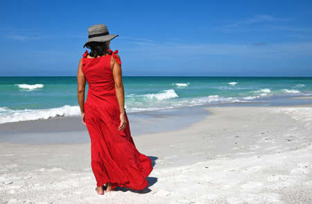 Beautiful Woman in a Red Summer Dress and Hat Standing on the Beach