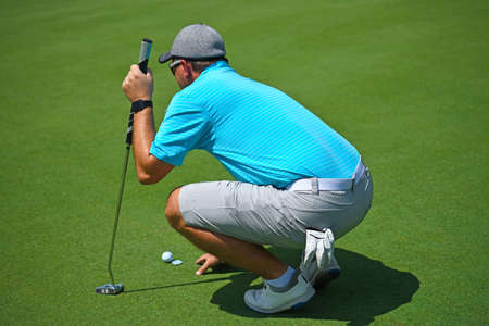 Shallow DOF Image of a Young Man Playing Golf Squatted Down Looking Over the Green before Making His Putt