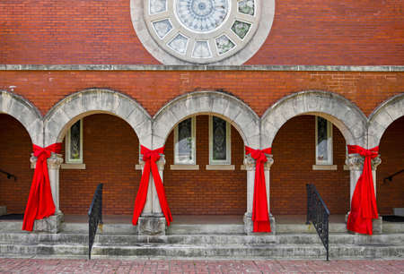 Large Red Ribbons are Hung on the Front of a Beautiful Church as a Sign of Prayer and Hope During the Covid-19 Pandemic in America 版權商用圖片