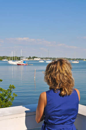 A Beautiful Woman Wearing a Blue Sun Dress Looking out at Sailboats in the Marina 版權商用圖片