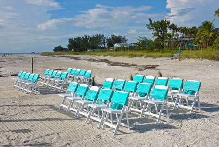 Chairs Arranged on the Beach in Preparation for an Evening Wedding 版權商用圖片