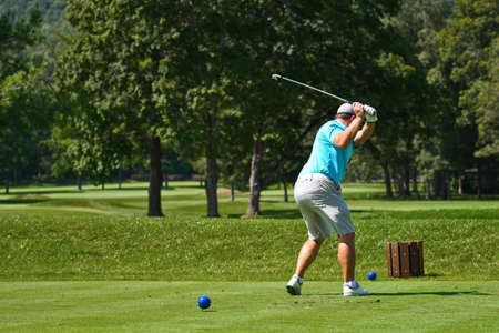 Young Man on Golf Course Hitting an Iron off the Tee Box While Playing a Round of Golf