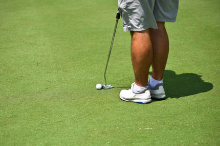 Young Man on the Golf Green getting into Position to make a Putt.