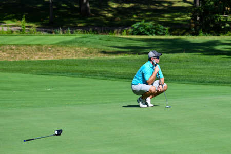 Young Man Looking Over the Green on a Beautiful Golf Course Before Taking His Putt Shot.   版權商用圖片