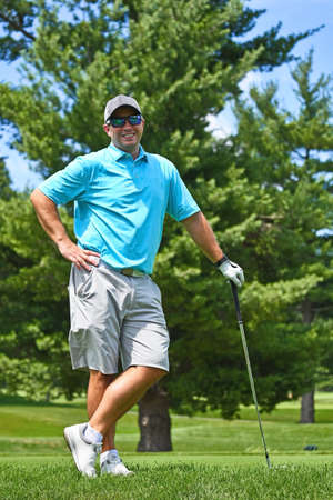 Young Man Playing a Round of Golf Stops and Poses for a Photograph.