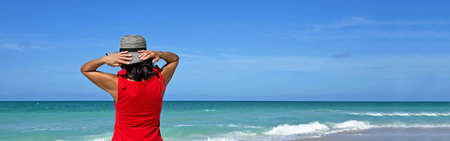Beach Banner of Beautiful Woman in a Red Summer Dress Standing on the Beach Holding Her Hat on her Head to keep it from Blowing Away.