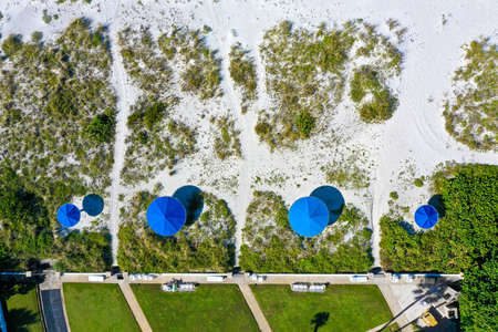 An Aerial View of Four Blue Beach Umbrellas on White Sandy Beach in Florida 版權商用圖片