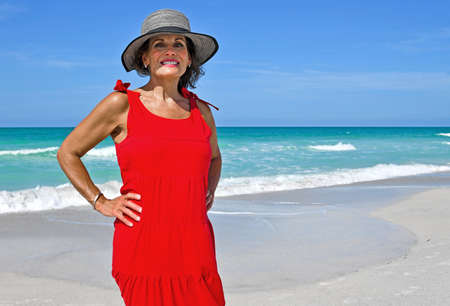 Beautiful Mature Woman Wearing a Red Summer Dress on the Beach