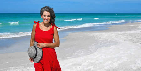 Beautiful Mature Woman Wearing a Red Summer Dress and Holding Her Hat on the Beach