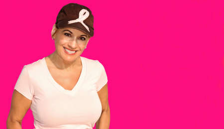 Beautiful Woman Wearing a Hat With a Pink Ribbon Isolated on a Pink Background in Support of Breast Cancer Awareness 免版税图像