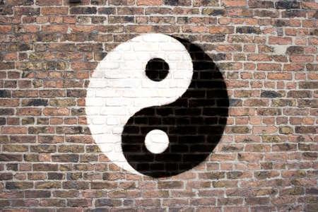 Yin and Yang symbol sprayed on brick wall photo
