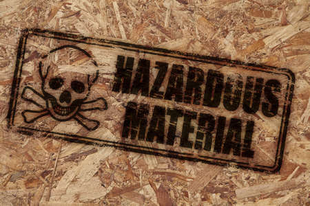 Hazardous material stamp on rough wooden background photo