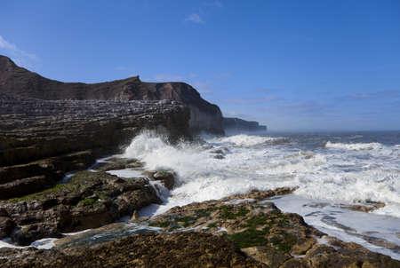 Waves crashing against rocky coast on a sunny day. photo