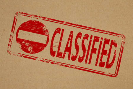 secretive: Classified rubber stamp symbol on brown paper background Stock Photo