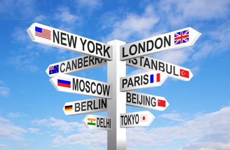 World capital cities and flags signpost against blue sky Stock Photo