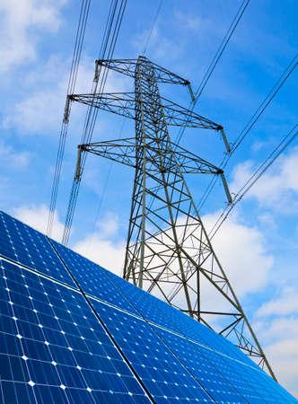 solar array: Solar panels and electricity pylon against blue sky  Stock Photo