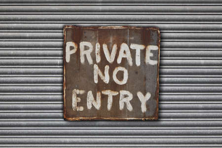 galvanised: Rusty metal private, no entry sign on metal shutter background