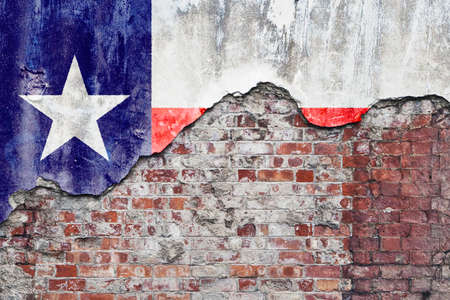 Grungy old brick wall with State of Texas flag on broken render surface Foto de archivo