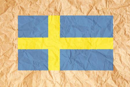 bandera suecia: Bandera de Suecia. Bandera sueca sobre arrugado fondo de papel marr�n.
