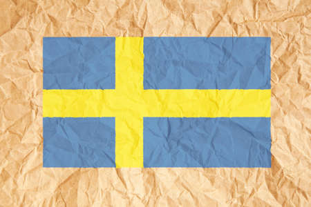 scrunched: Sweden flag. Swedish flag on crumpled brown paper background.
