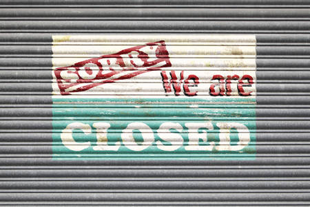 sorry: Metal shutter with sorry we are closed painted shop sign. Stock Photo