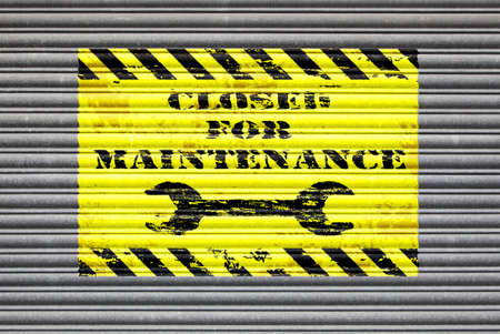 under construction sign: Metal shutter with closed for maintenance painted sign. Stock Photo