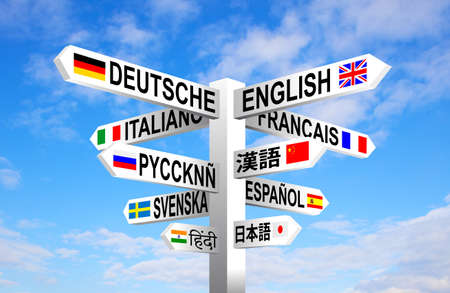 spanish language: Multilingual languages and flags sign post against blue sky Stock Photo