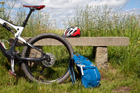 Mountain bike leaning against a stone bench with back pack and helmet   Stock Photo