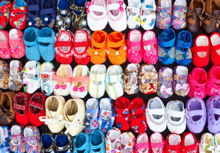 Colorful different baby shoes laid out in pairs