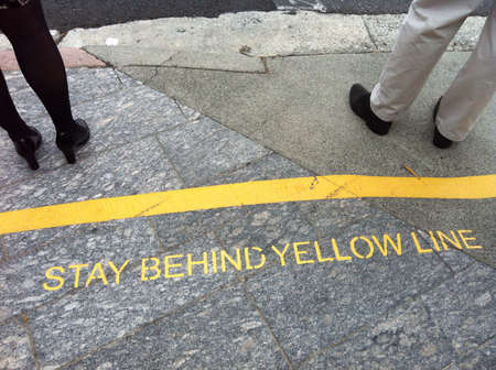 deregulation: Male and female stand in front of the warning yellow line at the bus stop