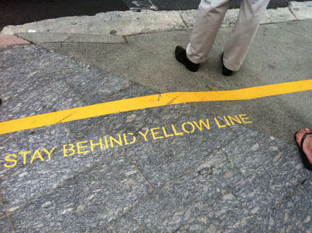 violating: A man violating the warning to stand in front of yellow line at the bus stop