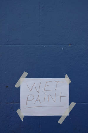 wet paint sign on blue brick wall Stock Photo