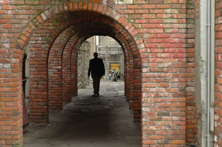 man walks in a brick tunnel photo