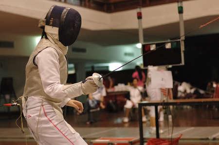 fencing foil: Foil swordman fighting in fencing match