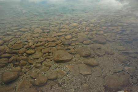 round stones under clear lake photo