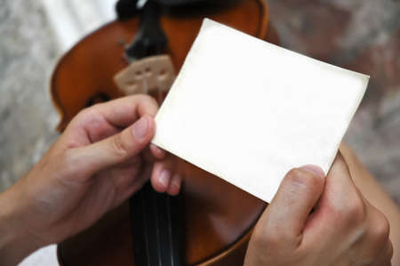 Hands of musician holding white blank note Stock Photo - 25393115