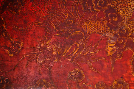 china art: Ancient vintage golden painting of Chinese dragon on red wooden wall Stock Photo