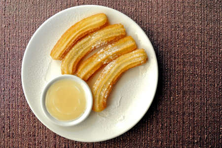 Fresh made Spanish churros with white chocolate dipping suace Stock Photo