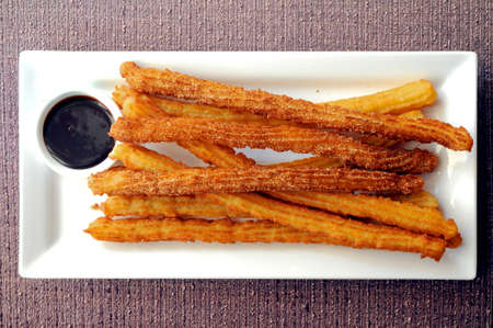 Spanish donut Churros freshly made with dark chocolate dipping sauce photo