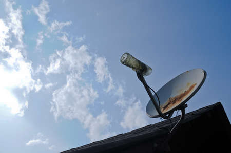 Rustic old parabolic satellite station and blue sky photo