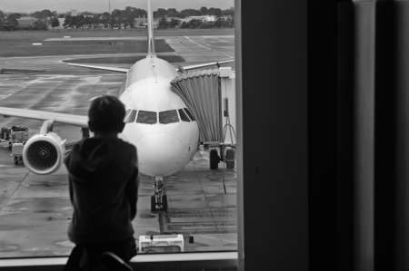 A boy starring at a jetplane waiting to board at the airport
